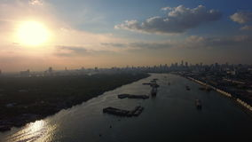 Fly over river with container cargo ship import export transportation and sunset wide aerial view background, 4K stock footage