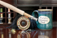 Fly Rod and Coffee. Fly rod and reel on desk with coffee cup that reads World's Greatest Dad Stock Photo
