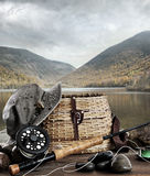 Fly rod with creel and equipment on wood. Table Royalty Free Stock Images