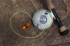 Fly Rod and Orange Spider Fly on a Dry Rock Stock Images