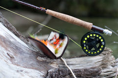 Fly fishing. Rod on old tree near open with streamers wallet Stock Photos