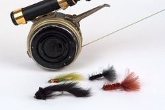 Fly rod, reel and flies. Fly rod and reel close up with an assortment of 4 trout flies on a white background Royalty Free Stock Photos