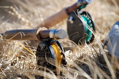 Fly rods in dry grass. Flyfishing - two rods lying in the grass royalty free stock image