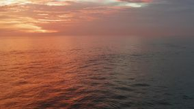 Fly in sunset time. Beautiful red sky, clouds,sea. 4K Aerial panorama. Ocean, sea surface in sunrise, sunset time with stock footage
