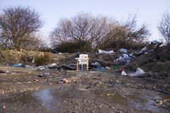 Fly tipped high chair. Fly tipping in remote lane. Child's high chair in the centre Stock Photography