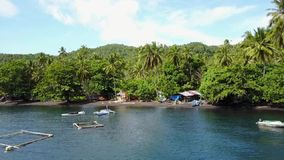 Fly to village on island in Lembeh Strait. Flying above fish cages to tropical island with black sand beach, shelters, boats and green palm trees in Lembeh stock video