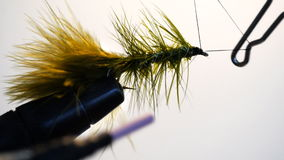 Fly tying. Whip finishing a green woolly bugger wet fly stock footage