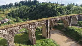 Fly under old arched bridge. Nature in the Carpathian mountains stock video