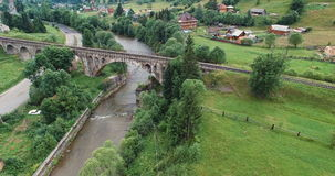 Fly under old arched bridge. Nature in the Carpathian mountains stock video footage