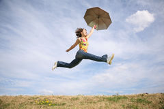 Fly woman with umbrella. Jumping woman with umbrella against sky Stock Photo