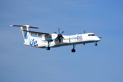 Flybe Bombardier Q400. A Flybe Bombardier Q400 on approach in sunny weather stock photos