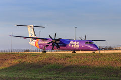 Flybe Bombardier Q400 new livery. A Flybe Bombardier Q400 with new purple livery taxiing royalty free stock photography