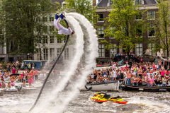 A flyboard guy makes a backflip on the Amstel river. A flyboard guy makes a backflip high in the air on the Amstel river on the Amsterdam Gay Pride Canal Parade royalty free stock photos
