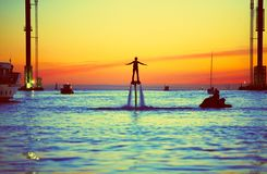 Flyboard in the night sky of St. Petersburg. flying and flitting over the water people, on the background of a beautiful sunset, t royalty free stock image