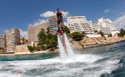 Flyboard practice wide view. A young man practices flyboard, a new aquatic sport where a board is powered by water jet system, in the island of Mallorca, Spain royalty free stock images