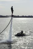 Flyboard and ski jet performing stunts Royalty Free Stock Photo