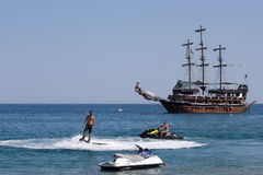 Flyboard and yachting stylized pirate schooner royalty free stock photos
