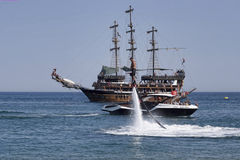 Flyboard and yachting stylized pirate schooner Stock Photos