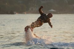 Flyboarder with arms out twisting towards water Stock Photo