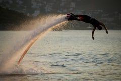 Flyboarder che si tuffa alto arco backlit perfetto Fotografie Stock Libere da Diritti