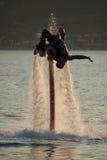 Flyboarder, das den hinteren leichten Schlag umgeben durch Spray tut Stockbild