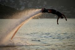 Flyboarder diving in perfect high backlit arc Royalty Free Stock Photos