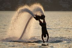 Flyboarder diving vertically with arms stretched out Stock Images
