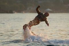 Flyboarder med armar som vrider ut in mot vatten Arkivfoto