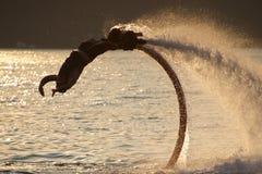 Flyboarder que hace salto mortal hacia atrás sobre ondas retroiluminadas Foto de archivo libre de regalías