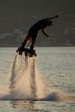 Flyboarder stekflott med sprej backlit för dyk arkivfoton