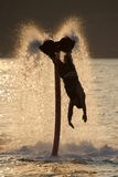 Flyboarder stretches towards waves after back flip Royalty Free Stock Images