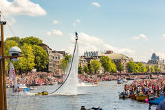 Flyboarding on the Amstel in Amsterdam. A spectaculair flyboard man at the Magere Brug on the Amstel river at the Amsterdam Gay Pride Canal Parade 2015 in the royalty free stock images