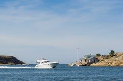 Flybridgeboat and summerhouse Swedish west coast Stock Image