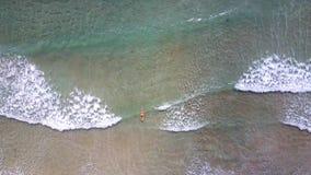 Flycam下降给冲浪在海浪的妇女在太阳光芒下 股票视频