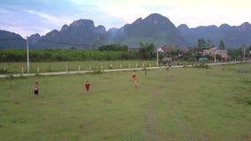 Flycam在绿色山谷显示踢橄榄球的孩子 股票视频