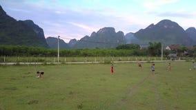 Flycam摄制踢在绿色领域的地方孩子橄榄球 影视素材