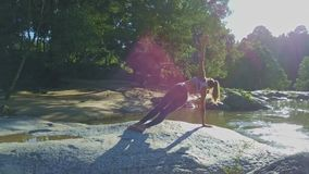 Flycam显示举行瑜伽姿势的女孩反对平安的河 股票录像