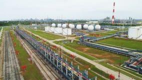 Flycam двигает над нефтеперерабатывающим комплексом с резервуарами и трубопроводами сток-видео