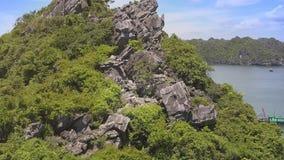 Flycam показывает красивые остров и женщину скалы среди утесов сток-видео