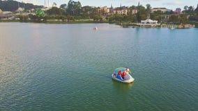 Flycam показывает людей на катамаране лебедя на плоском большом озере видеоматериал