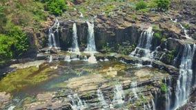 Flycam abre la vista de cascadas contra las plantas tropicales de las rocas
