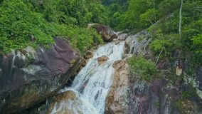 Flycam Approaches Waterfall Cascade Flowing across Boulders. Flycam approaches through lake foamy waterfall cascade flowing across boulders among tropical green stock footage