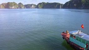 Flycam bewegt sich über Boot mit bräunendem Mädchen entlang Ozean-Bucht stock video footage