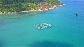 Flycam bewegt sich auf sich hin- und herbewegenden Hummer-Bauernhof unter ruhigem blauem Ozean stock video