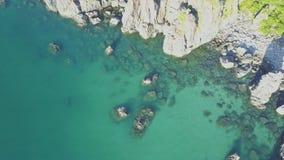 Flycam desciende al océano de la turquesa con Rocky Coastline metrajes