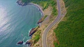 Flycam flyttar sig nära ovanför kusthuvudvägen vid det blåa havet lager videofilmer