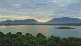 Flycam flyttningar ovanför den fridsamma sjön mot Hilly Landscape Sunrise
