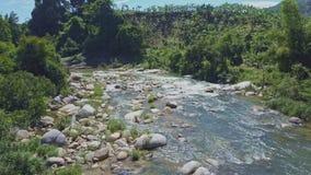 Flycam flyttningar ovanför floden som täckas med, vaggar mot djungel