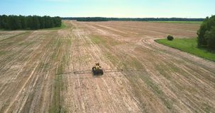 Flycam follows fertilizer spreader driving along harvested field. Pictorial view flycam follows fertilizer spreader driving along vast striped harvested field stock footage