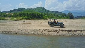 Flycam Follows Jeep Crossing River against Tropical Plants. NHA TRANG, KHANH HOA/VIETNAM - APRIL 28 2017: Flycam follows military jeep crossing shallow river and stock footage